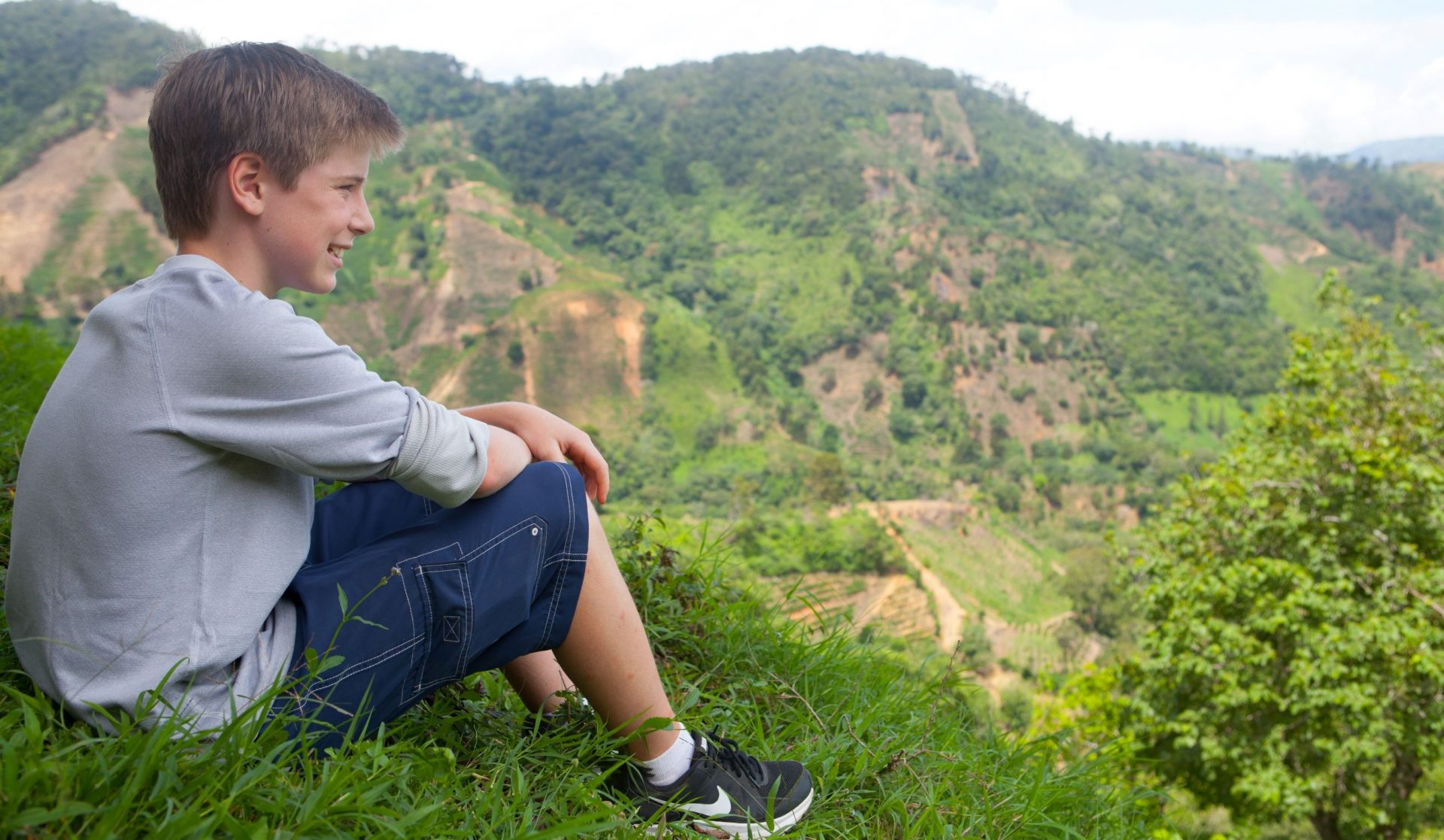 Middle school aged boy looks at vista of Costa Rican fields