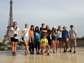 School group poses with the Eiffel tower in the background