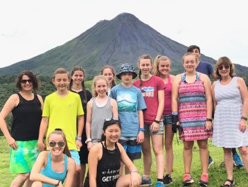 student group poses in front of volcan arenal costa rica