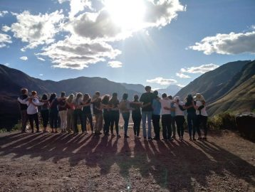 A dozen people standing side by side with their backs towards the camera facing a mountain range with a sunny sky above